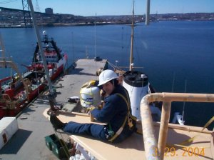 Replacing antenna on the CCGS Hudson,with CCGS Needler visible on the jetty